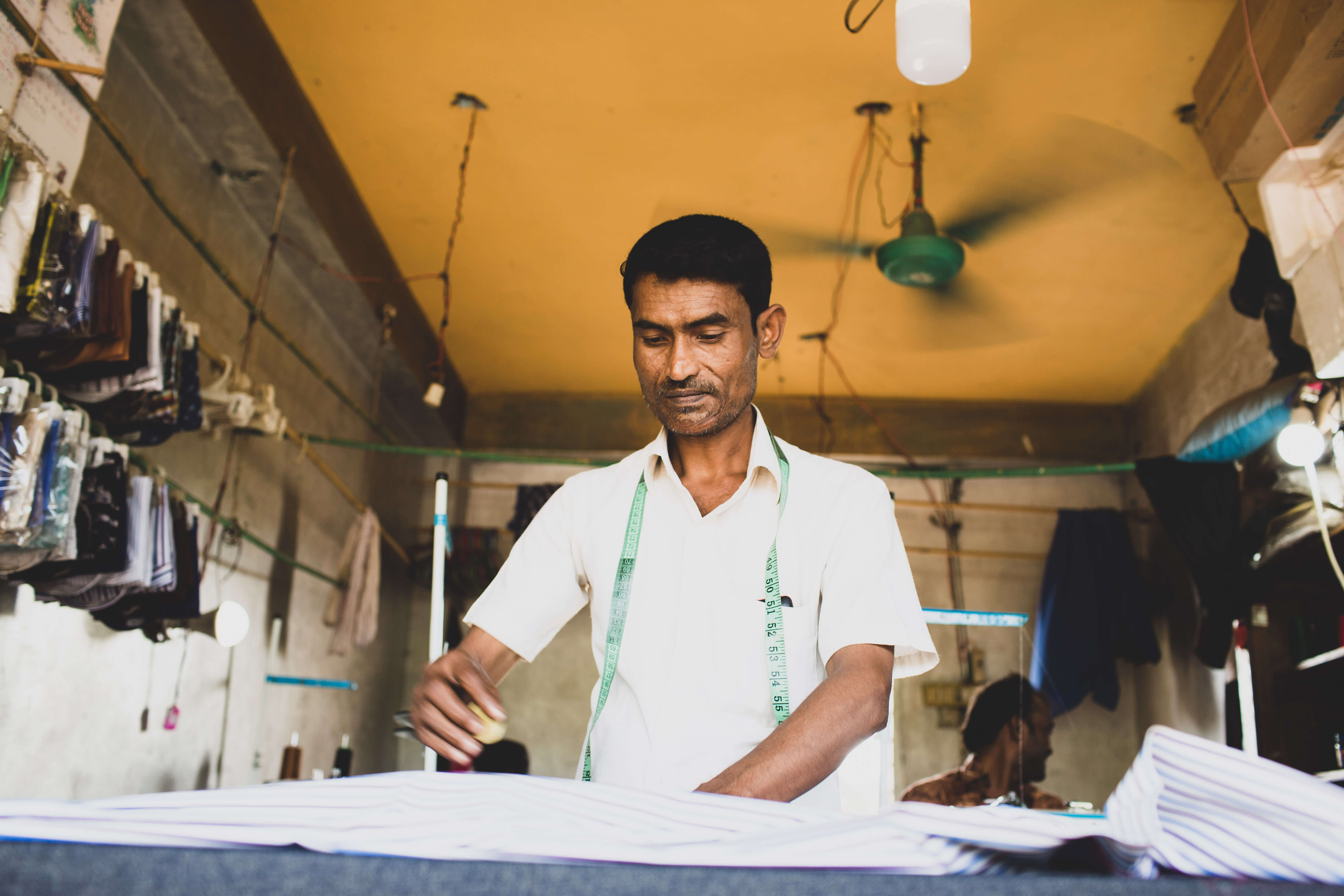 Refugee man tailors clothes