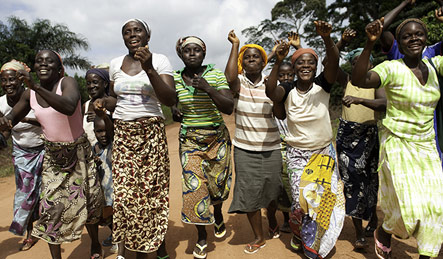 Women dance on their way to an Oxfam project