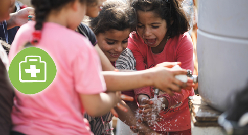 Children wash their hands in an informal refugee camp in Barsa
