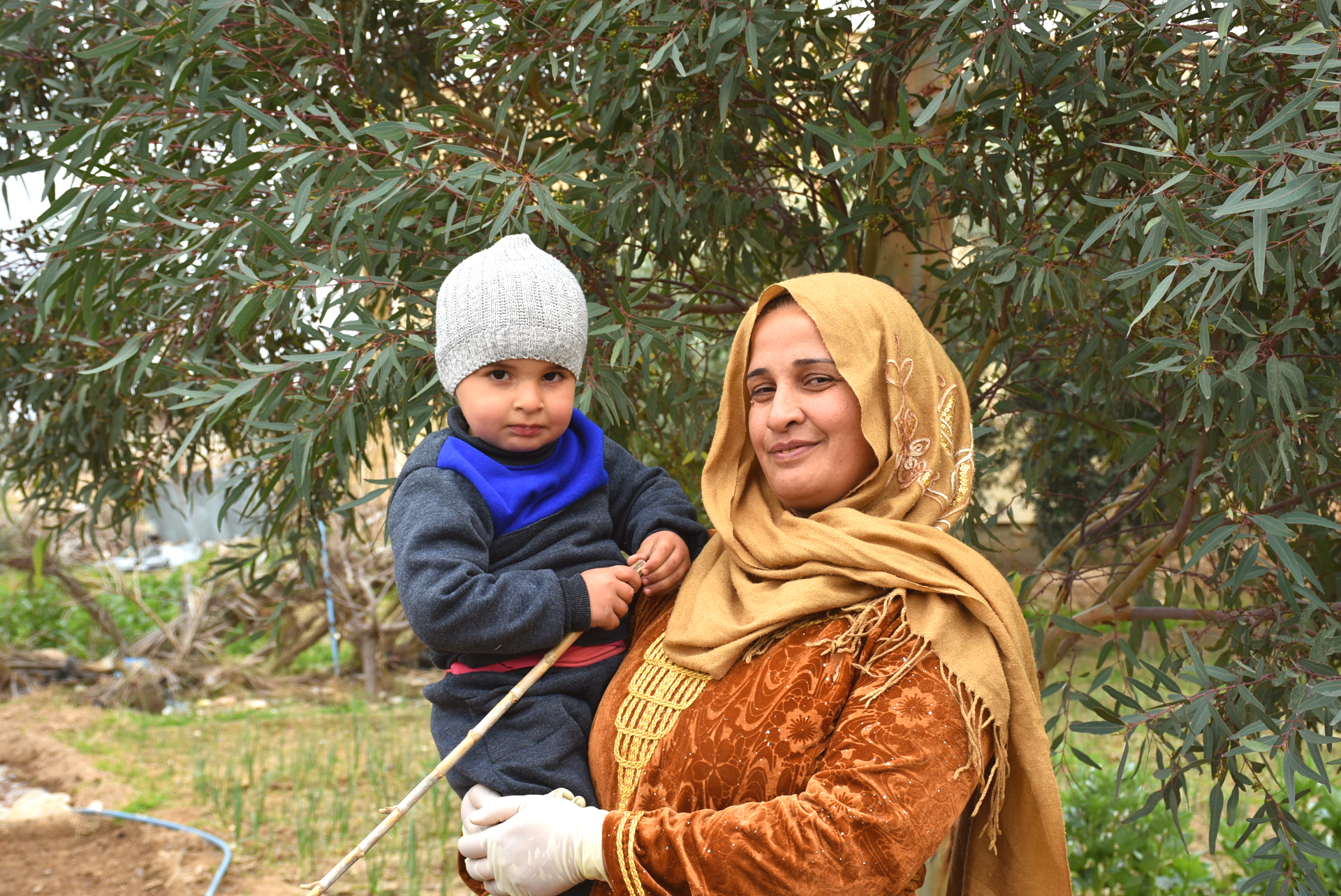 woman holds her son on farm in rural Syria