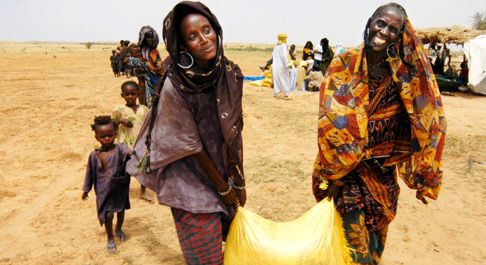 Debie & Doule carry a bag of rice near Bermo, Niger