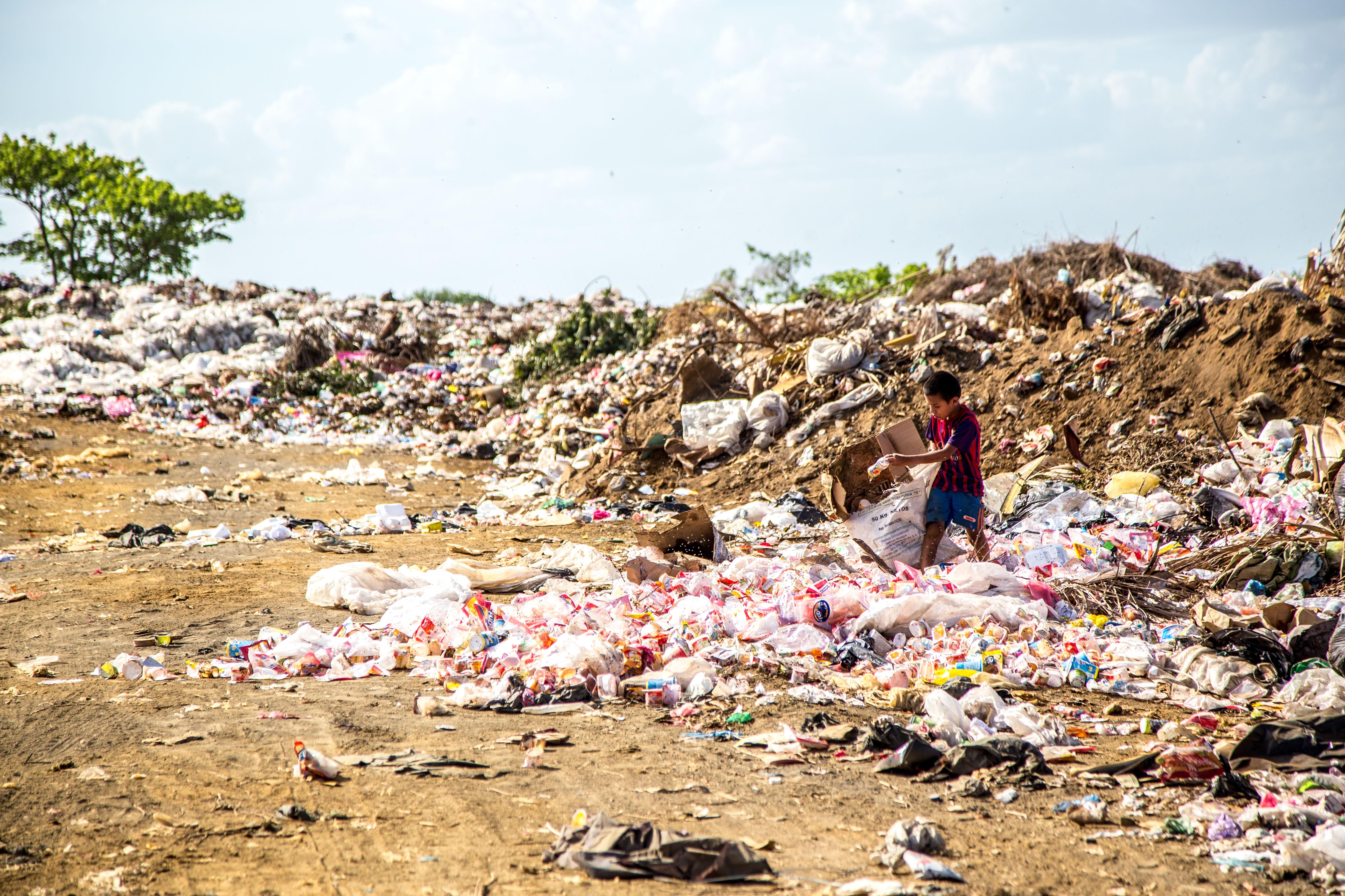 Boy walks through trash plastic waste landfill