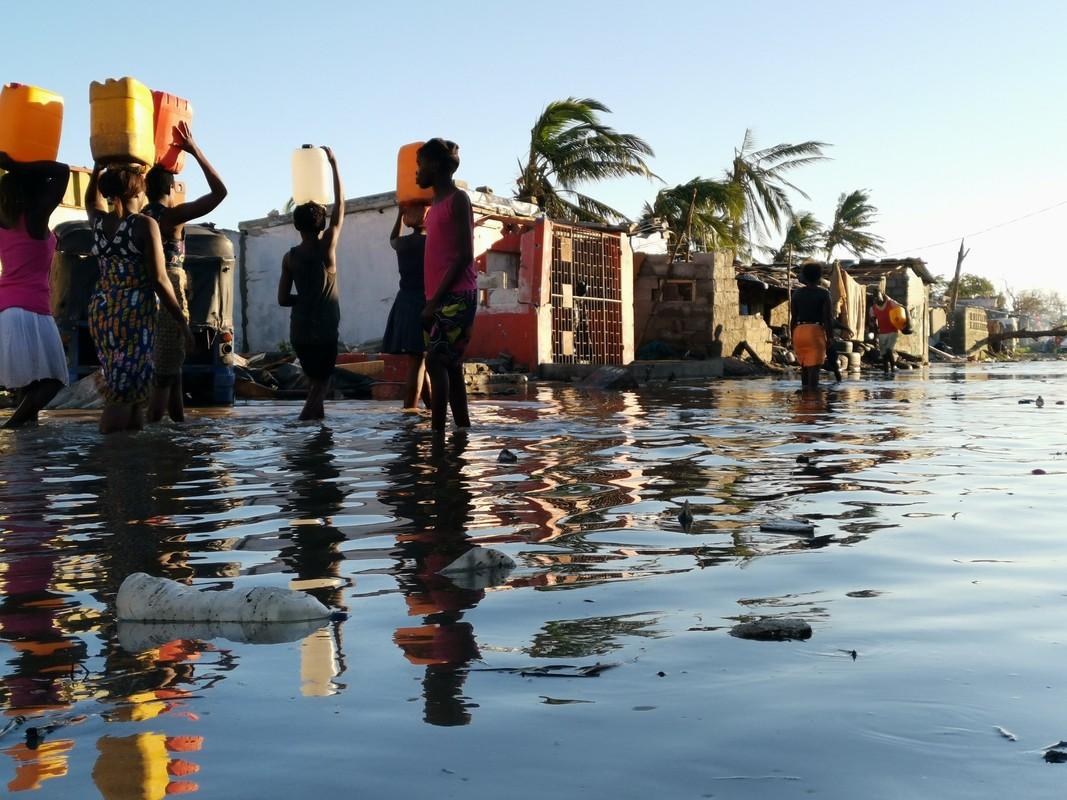 Cyclone survivors walk through floods
