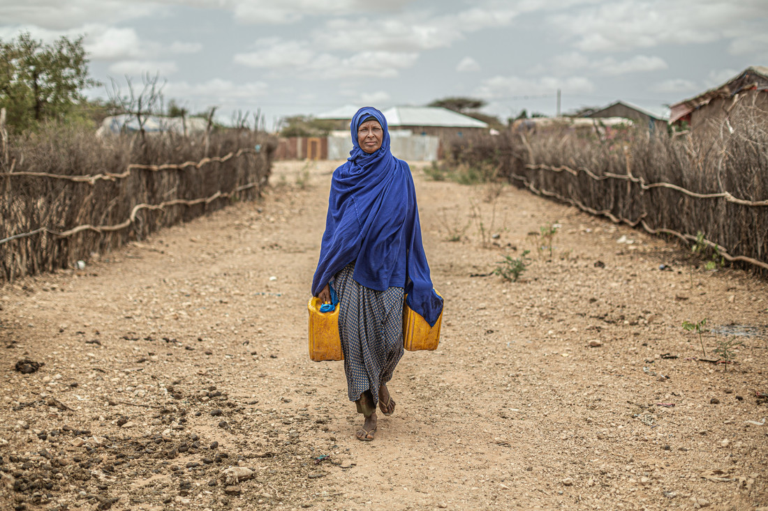 Woman carrying water back to her shelter