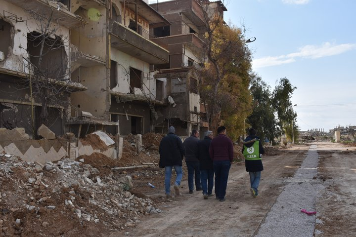 refugee man walks among Syria rubble