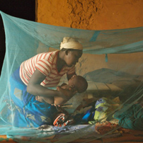 Fatimata Waled Dossane sits inside a mosquito net with her son