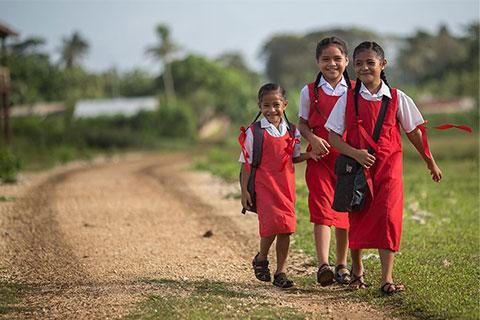 Girls walking to school on dirt road