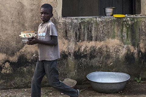 Disheveled boy carries plates