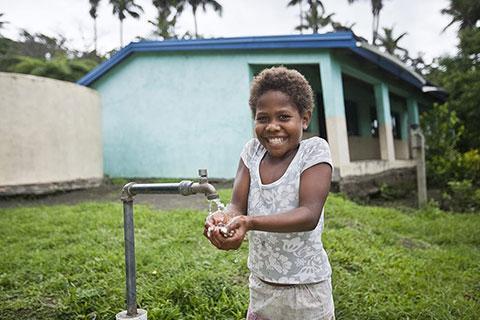 Child smiling washing hands
